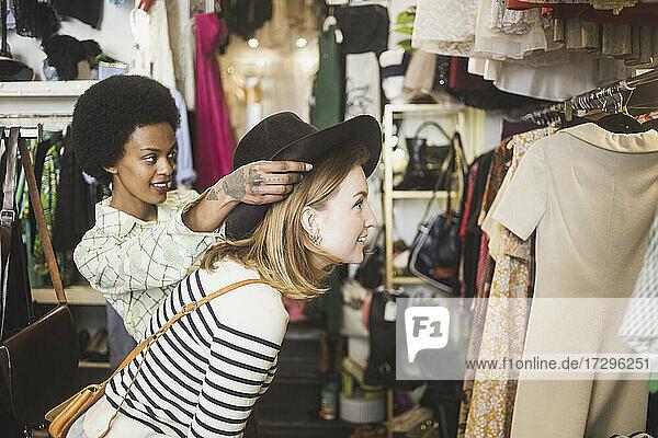 Ladenbesitzer versucht Hut auf weiblichen Kunden in Boutique Ladenbesitzer versucht Hut auf weiblichen Kunden in Boutique