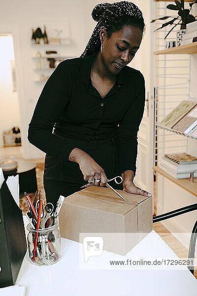 Junge Unternehmerin beim Öffnen eines Kartons mit einer Schere im Heimbüro