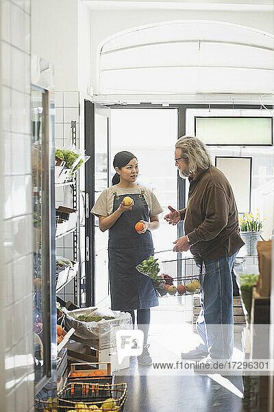Älterer männlicher Kunde im Gespräch mit der Besitzerin beim Kauf von Lebensmitteln im Geschäft