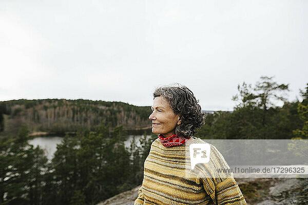 Smiling female explorer looking away against sky