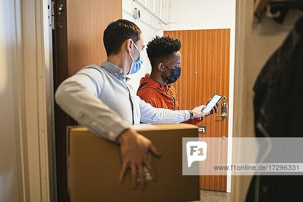 Männlicher Kunde erhält Paket von jungem Zusteller während COVID-19