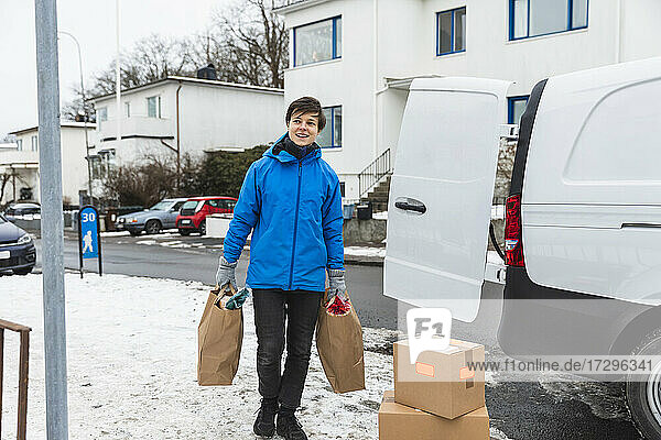 Smiling essential service woman delivering paper bags during winter