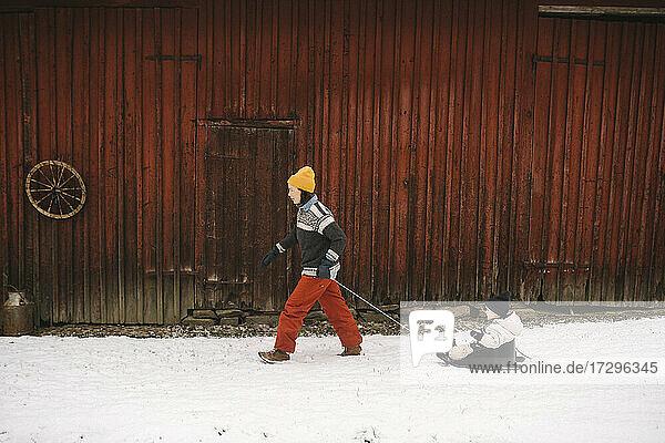 Ältere Frau zieht Tochter auf Schlitten beim Spaziergang durch Hütte im Winter