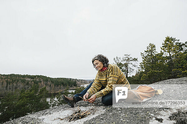 Mature woman holding stick while preparing for campfire in forest against sky