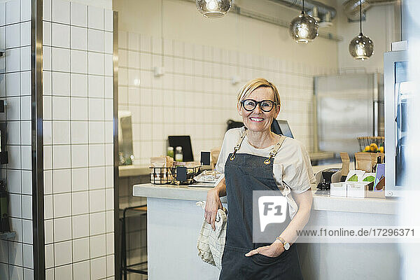 Smiling female owner with hand in pocket standing at store