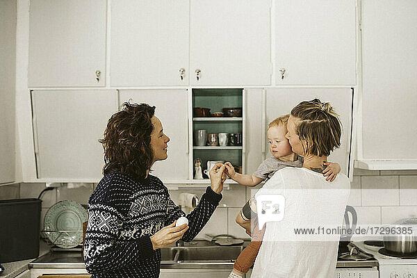 Lesbische Mütter mit Tochter in der Küche zu Hause