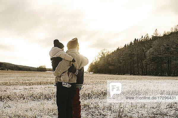 Lesbisches Paar mit Tochter stehend auf Schnee bei Sonnenuntergang