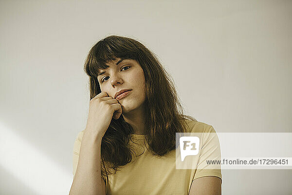 Young woman with hand on chin in front of white wall