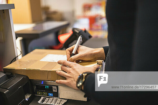Male store owner writing on package at checkout