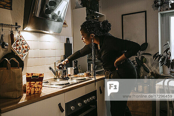 Young woman making tea in kitchen at home