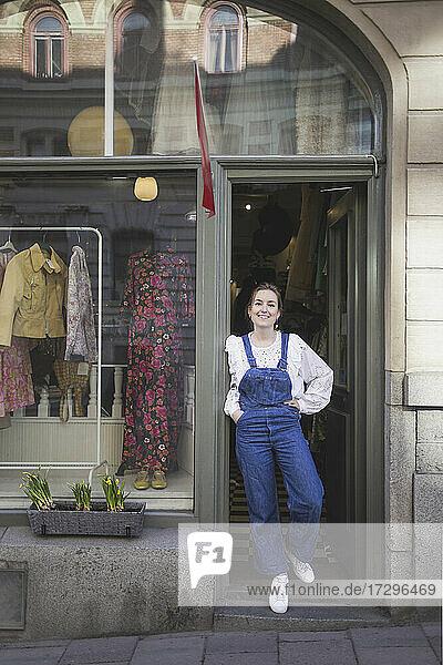 Junge weibliche Besitzerin mit Hand auf der Hüfte stehend am Eingang einer Boutique