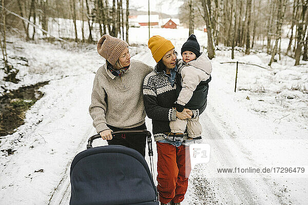 Mature woman carrying daughter while walking with girlfriend on snow