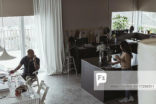 Male entrepreneur discussing with businesswoman while working from home