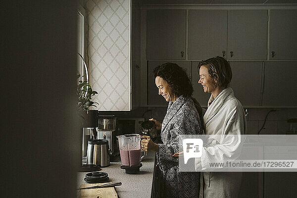 Lächelnde Frau schaut auf Freundin macht Smoothie in der Küche