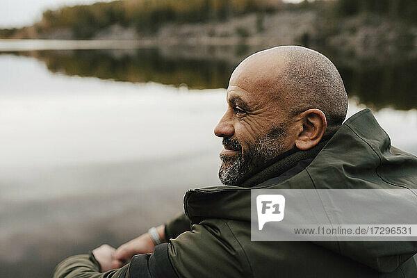 Lächelnder männlicher Wanderer  der im Urlaub am See wegschaut