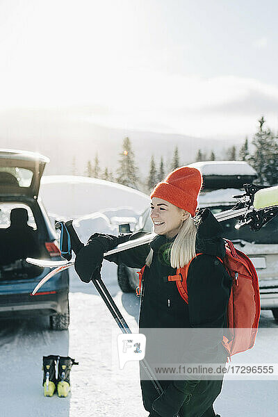 Young woman with skis looking away at parking lot
