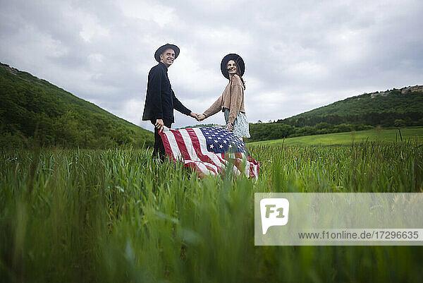 Junges Paar mit amerikanischer Flagge hält sich in einem Weizenfeld an den Händen