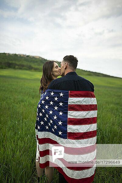 Junges  in die amerikanische Flagge gehülltes Paar küsst sich in einem Weizenfeld