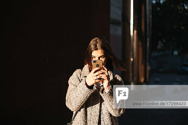 Young woman holding smart phone standing in city
