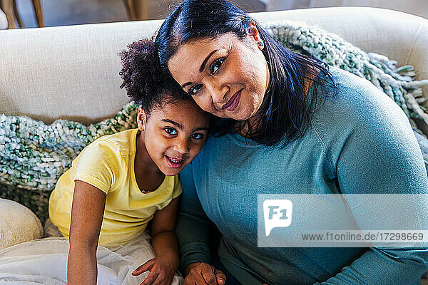 Portrait of smiling cute girl with grandmother on sofa at home