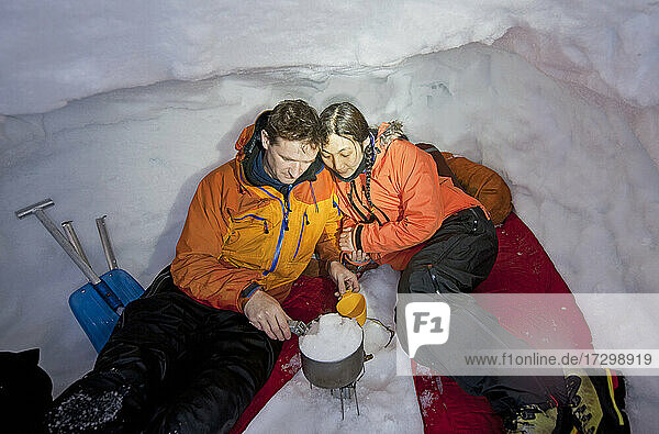 couple melting snow for cooking in snow shelter in Iceland