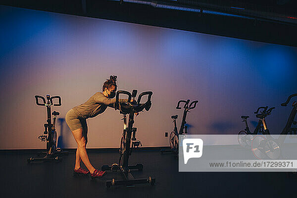 A young Caucasian woman stretches next to a stationary bike.