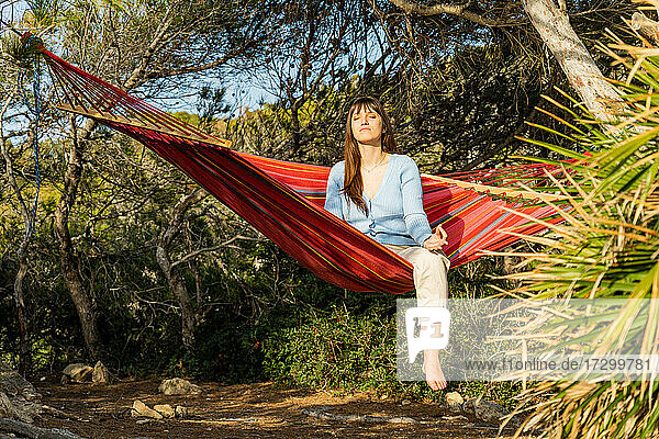 woman meditating in hammock at forest