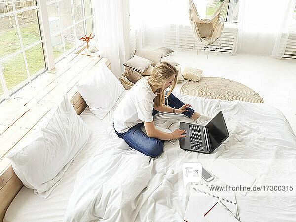 junge blonde Frau sitzt mit Laptop im Bett