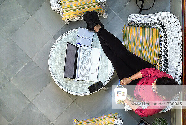 Top view of woman relaxing with a cup of coffee while using a computer at home.