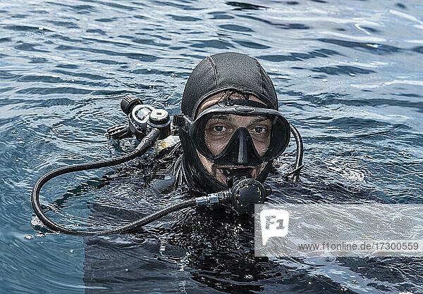 diver emerging from the ocean in Raja Ampat