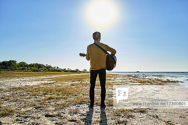 young man playing guitar in wild pl