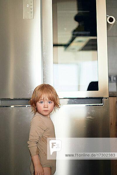 redhead boy looks into the fridge