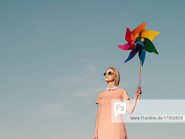 Style woman in pink dress with yellow glasses hold pinwheel on b