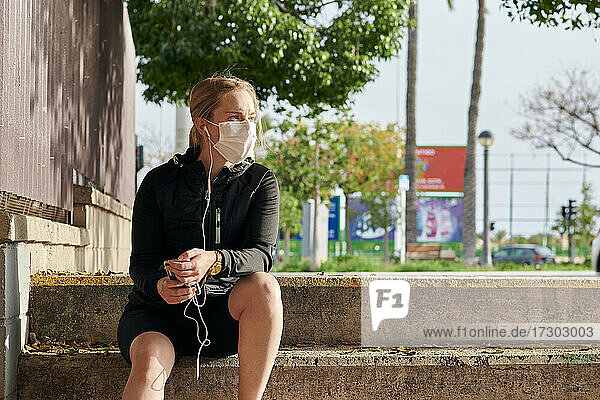 Woman in sportswear and face mask looks at her phone sitting on stairs
