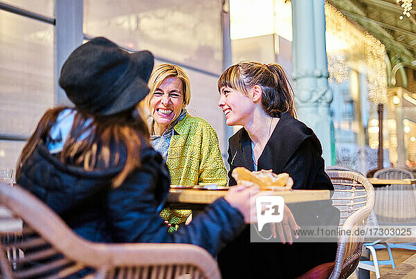 A mother having a drink with her two daughters sitting at the bar table after shopping