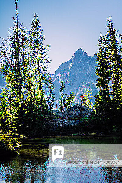 Female hiker top of the rock over alpine lake in North Cascades NP