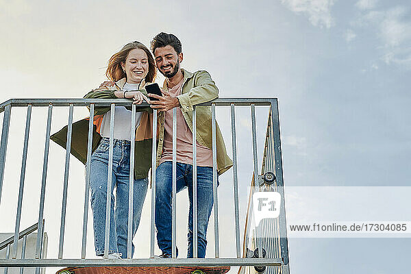Young multiracial couple smiles while they are looking at a phone