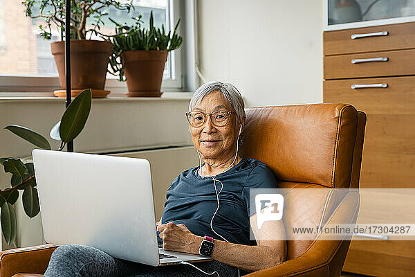 Portrait of senior woman wearing earphones while using laptop at home
