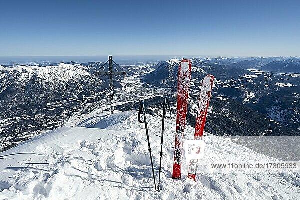 Ski stecken im Schnee  Alpspitz Gipfel mit Gipfelkreuz  Skitour zur Alpspitze  Blick auf Garmisch-Patenkirchen  Wettersteingebirge mit Schnee im Winter  Garmisch-Partenkirchen  Bayern  Deutschland  Europa