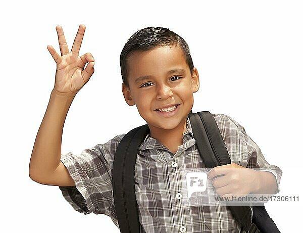 Glückliche junge hispanische Junge gibt ein okay Handzeichen mit Rucksack bereit für die Schule vor einem weißen Hintergrund