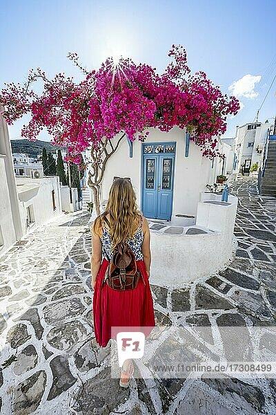 Weiß-blaue Häuser mit blühender lila Bougainvillea (Bougainvillea)  Junge Frau mit Rotem Kleid in der Altstadt von Lefkes  Paros  Kykladen  Griechenland  Europa