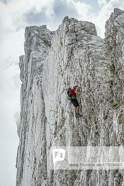 Junger Mann klettert an einer senkrechten Felswand ohne Seil  Felsige Berge und Geröll  beim Hochkalter  Berchtesgadener Alpen  Berchtesgadener Land  Oberbayern  Bayern  Deutschland  Europa