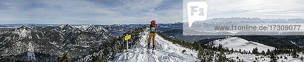 Alpenpanorama  Junge Frau auf Skitour  Am Gipfel des Simetsberg  Estergebirge  Bayerische Voralpen  Bayern  Deutschland  Europa