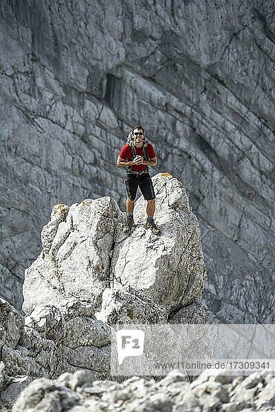 Junger Mann steht auf Felsen  Felsige Berge und Geröll  Wanderung zum Hochkalter  Berchtesgadener Alpen  Berchtesgadener Land  Oberbayern  Bayern  Deutschland  Europa