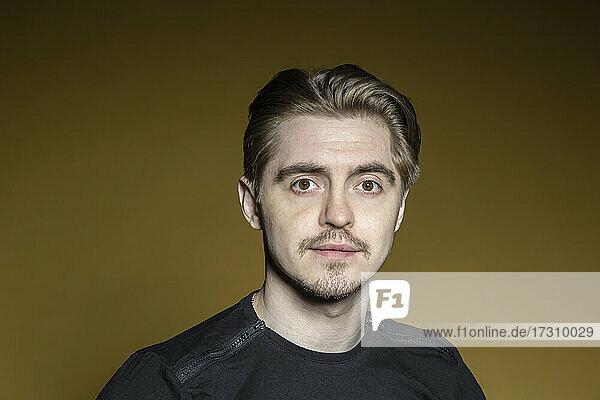 Porträt ernster Mann auf gelbem Hintergrund