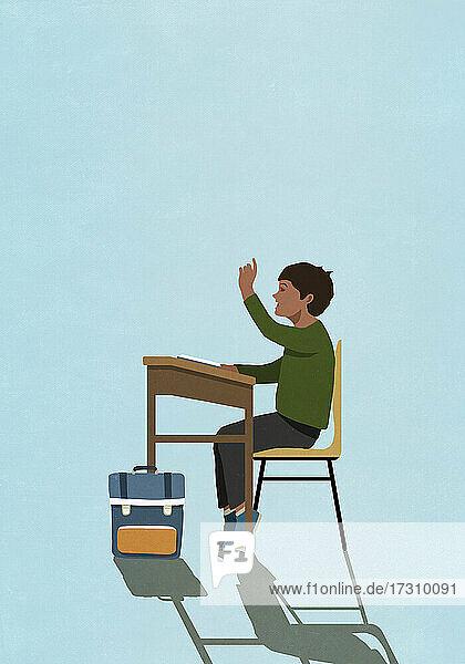 Schuljunge hebt die Hand auf der Schulbank