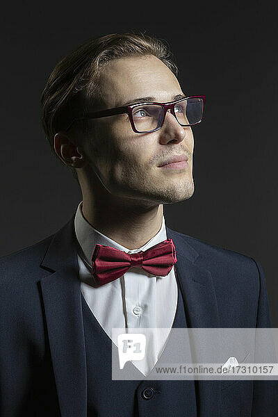 Porträt nachdenklicher  gut aussehender junger Mann in Anzug und Brille