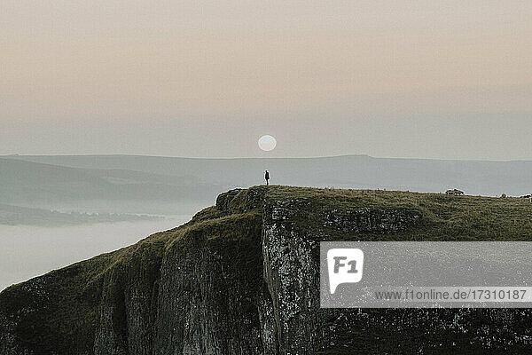 Wanderer auf Klippe bei Sonnenaufgang  Peak District National Park  England