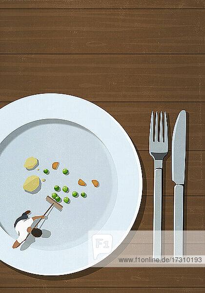 Blick von oben Mann mit Besen kehrt Essensreste auf Teller