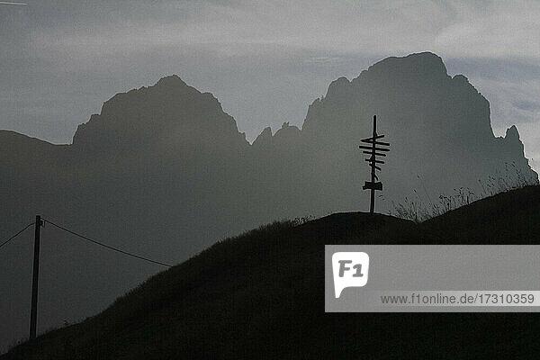 Silhouettierter Wegweiser und schroffe Berge  San Magno  Val Grana  Italien